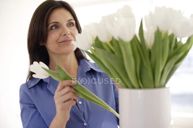 Woman arranging white tulips in vase. — Stock Photo
