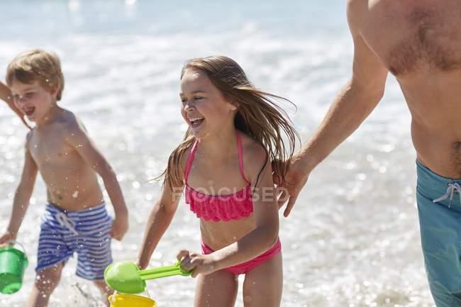 Bambini che giocano in spiaggia con secchio e vanga con i genitori . — Foto stock
