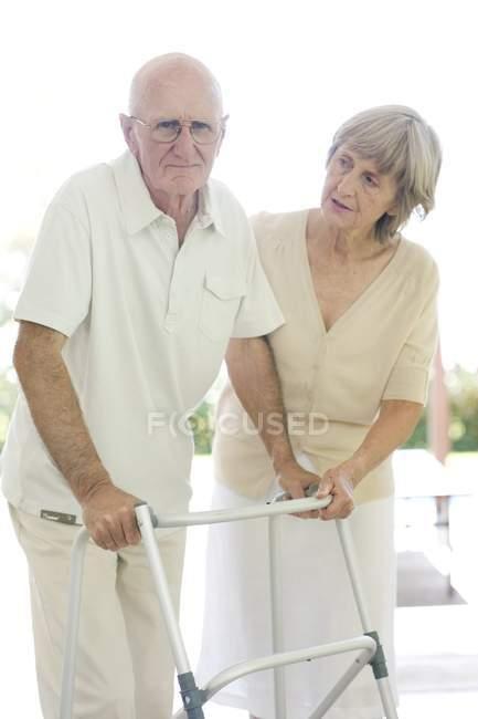 Senior woman helping senior man with walking frame. — Stock Photo