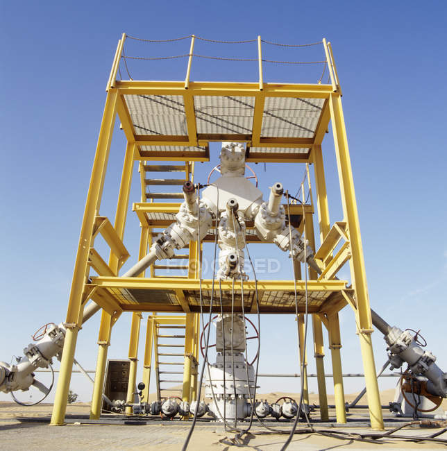 Array of pipes and valves fitted to production wellhead. — Stock Photo