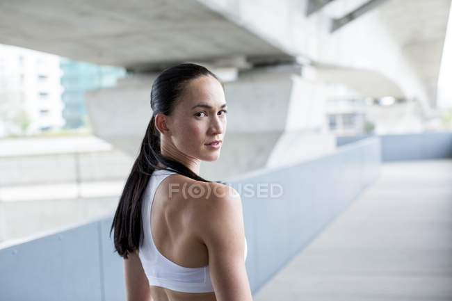 Donna in coltura superiore che osserva sopra la spalla — Foto stock