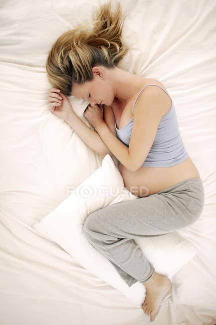 Vista aérea de la mujer embarazada durmiendo en la cama . - foto de stock