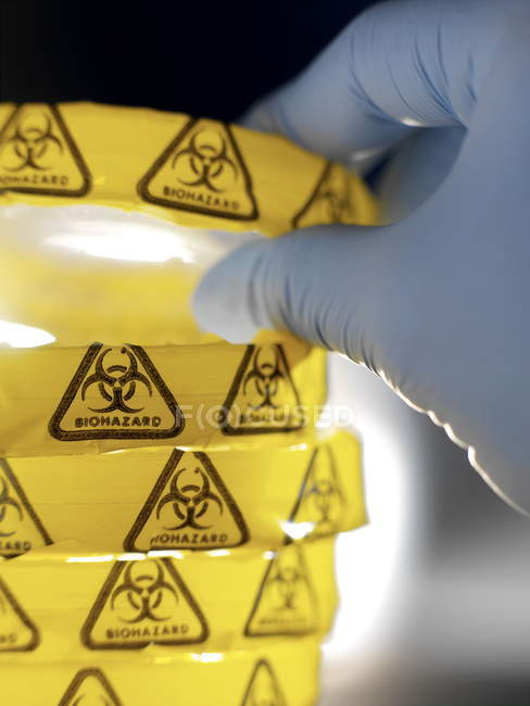 Scientist holding petri dish with biohazard warning in microbiology lab. — Stock Photo