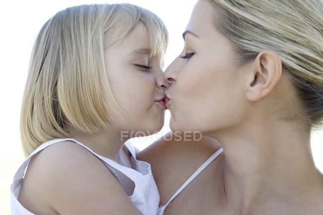 Мати і дочка цілуватися на відкритому повітрі. — стокове фото