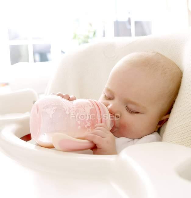 Sommeil de bébé fille tenue biberon de lait dans la bouche. — Photo de stock