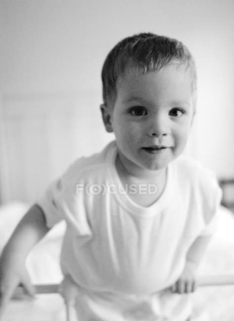 Portrait of toddler boy in cot. — Stock Photo