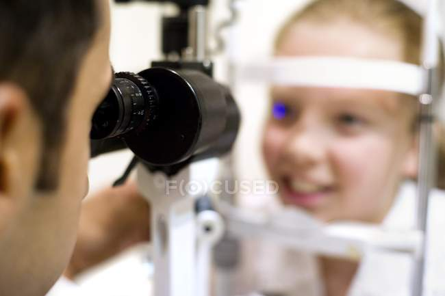 Optician using slit lamp for eye examination preteen girl. — Stock Photo