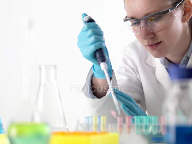 Female scientist pipetting liquid into Eppendorf tubes. — Stock Photo