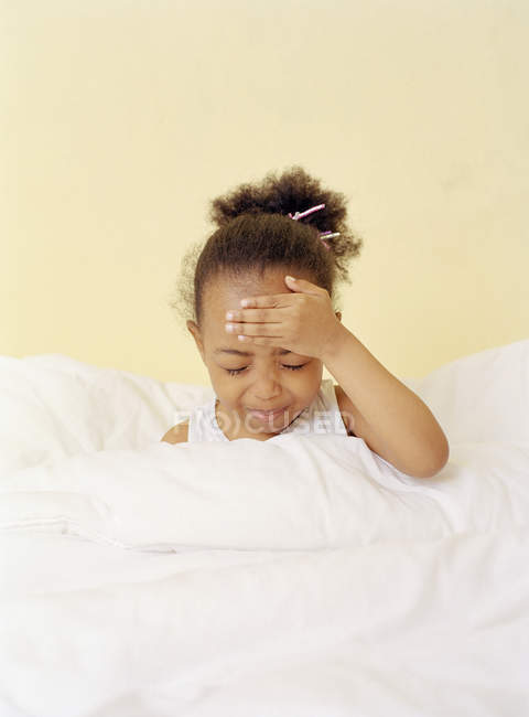 Elementary age girl holding head in bed with fever. — Stock Photo