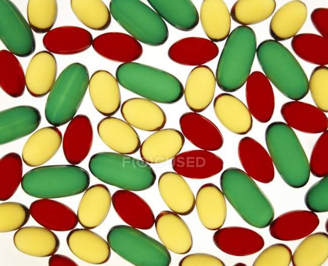 Разнообразные цветные капсулы для масла на белом фоне . — стоковое фото