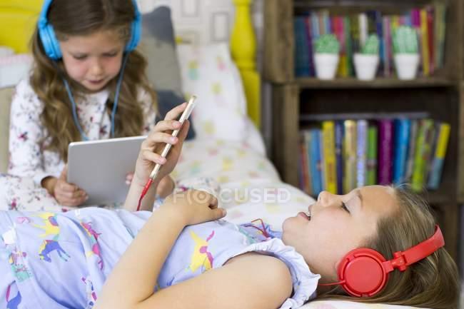 Zwei Schwestern im Schlafzimmer hören Musik und verwenden ein digitales Tablet. — Stockfoto