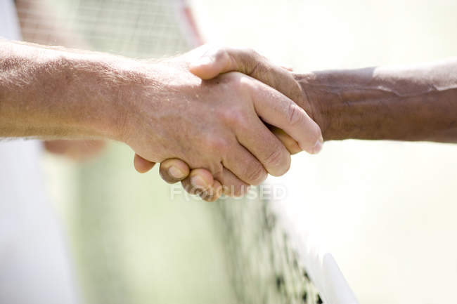 Close-up of two men shaking hands over tennis net. — Stock Photo