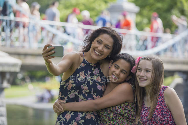 Hispanic mother with teen girls taking selfie with mobile phone in park. — Stock Photo