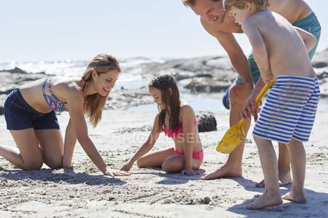 Дети, играющие на пляж с песком и лопата с родителями. — стоковое фото