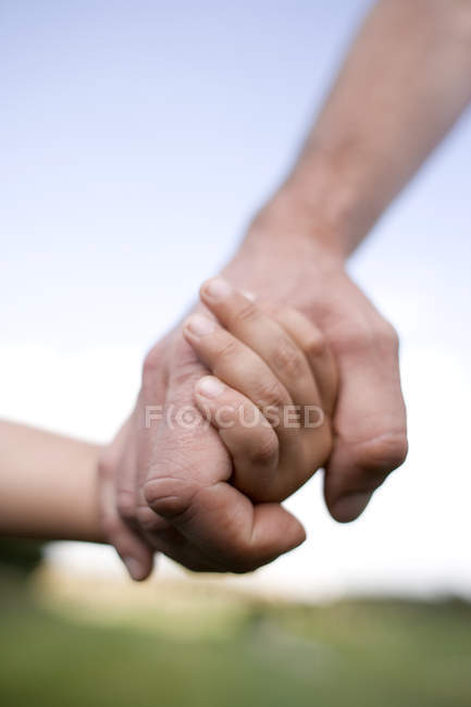 Padre e hijo cogidos de la mano, primer plano. - foto de stock