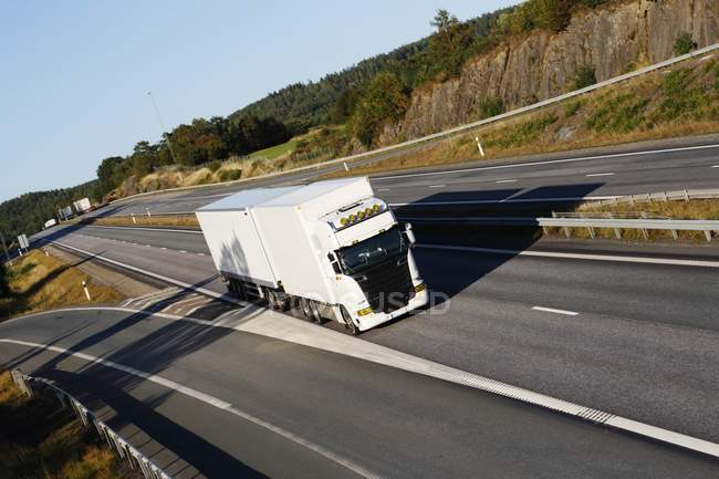 White truck riding on empty highway. — Stock Photo