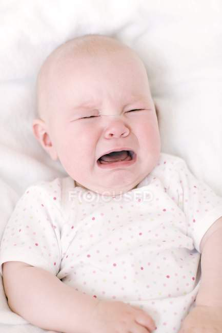 Unhappy infant baby crying in bed. — Stock Photo