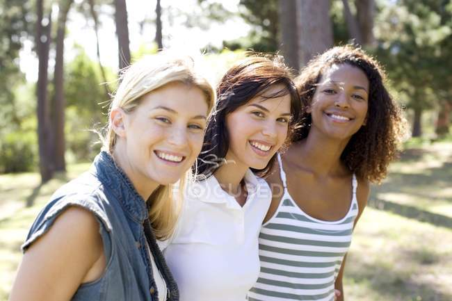 Three young female friends walking and smiling in park. — Stock Photo