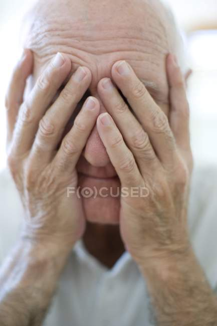Portrait of senior man covering face with hands. — Stock Photo