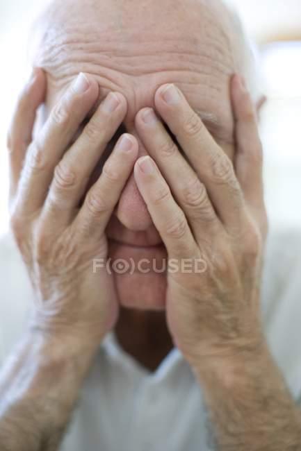 Retrato de homem sênior, cobrindo o rosto com as mãos. — Fotografia de Stock