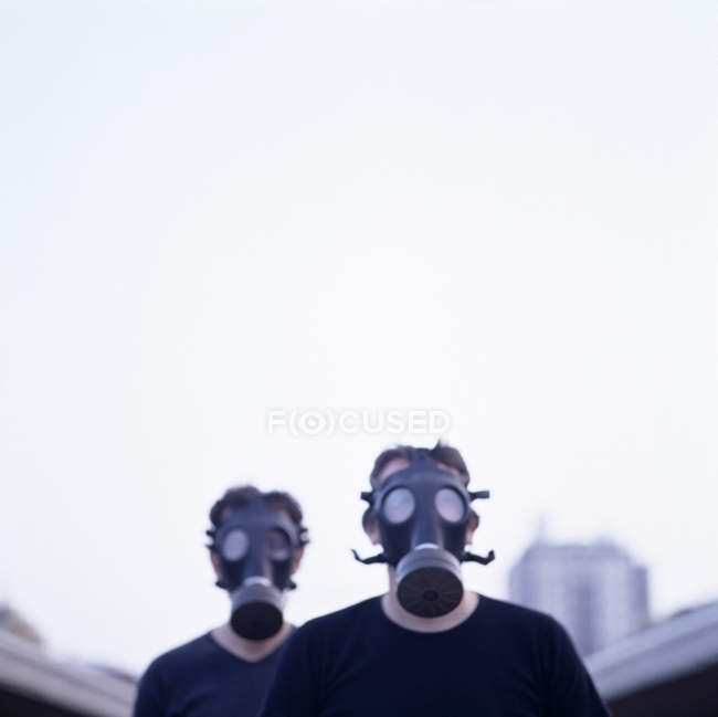 Two men wearing gas masks in city. — Stock Photo