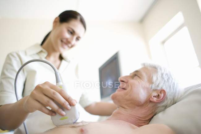 Senior patient undergoing heart ultrasound scanning by female doctor. — Foto stock