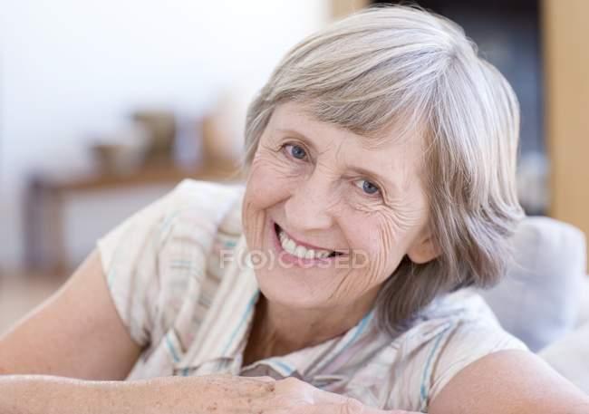 Portrait of happy senior woman relaxing on sofa. — Stock Photo