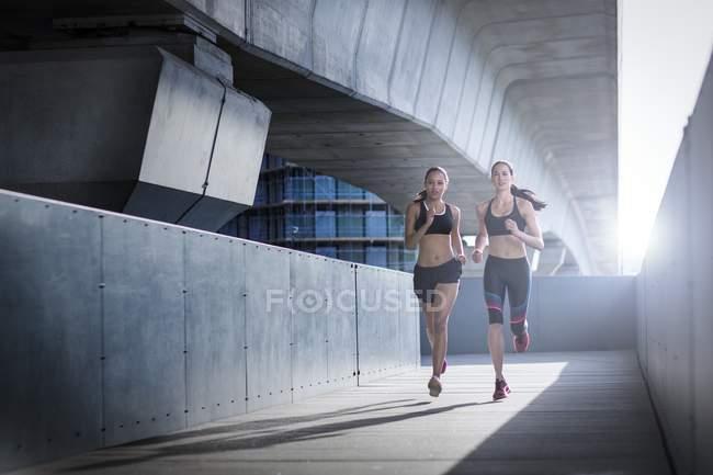 Молодые женщины, бегущие в городских условиях — стоковое фото