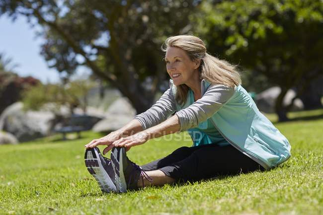 Senior woman stretching on grass. — Stock Photo