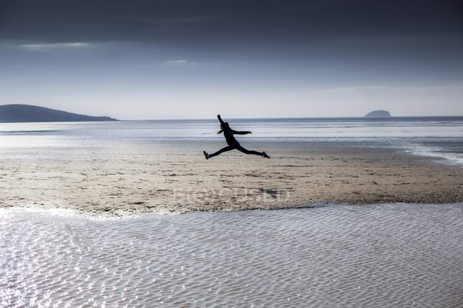Person silhouette leaping on beach. — Stock Photo