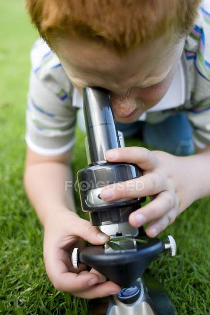 Ginger boy using light microscope on green grass. — Stock Photo