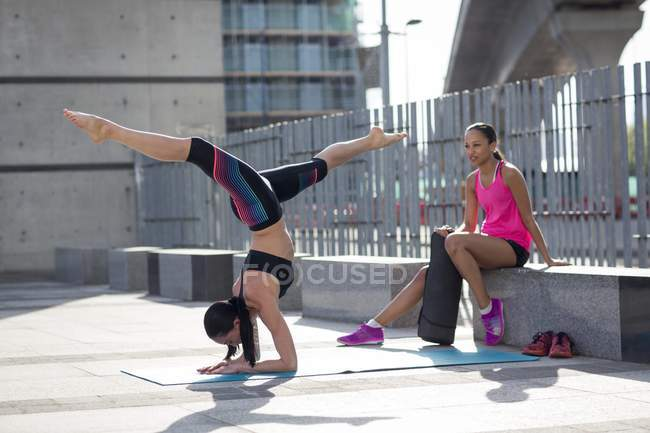 Woman in yoga position with friend watching. — Stock Photo