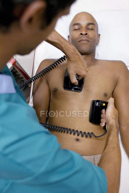 Doctor administering emergency defibrillation to patient. — Stock Photo