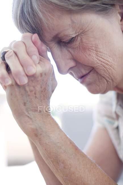 Mujer cogida de la mano a la frente - foto de stock