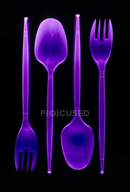 Colheres de plástico violeta e garfos no fundo preto . — Fotografia de Stock