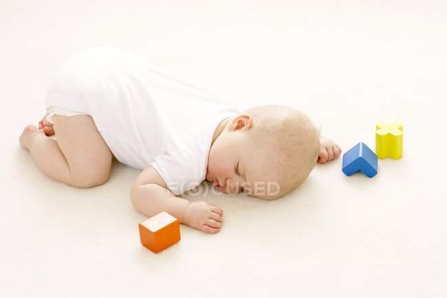 Bambino ragazza dormire sul pavimento circondato da blocchi di giocattoli . — Foto stock