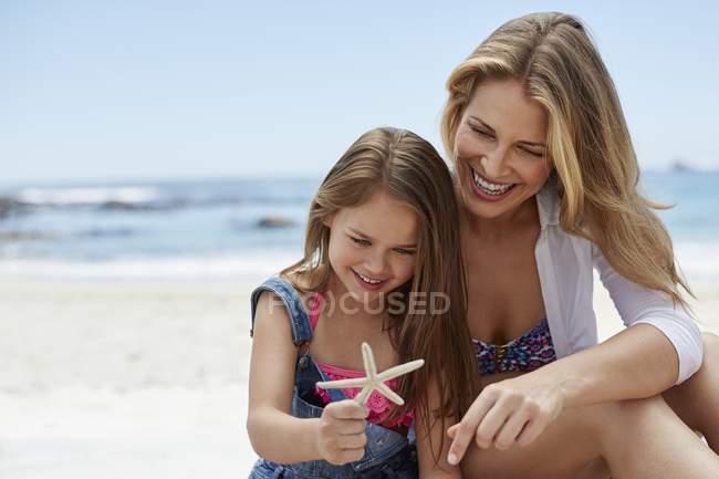 Матір з дочкою на пляжі проведення Морська зірка. — стокове фото