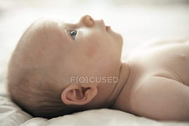 Младенческой мальчика, лежа на кровати. — стоковое фото