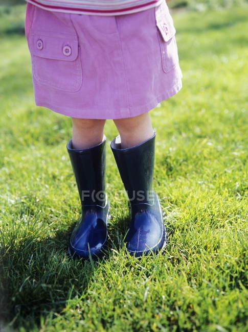 Малюк дівчата в гумові чоботи на зелений Луці. — стокове фото