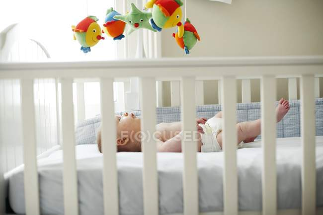Infant baby boy lying down in cot. — Stock Photo