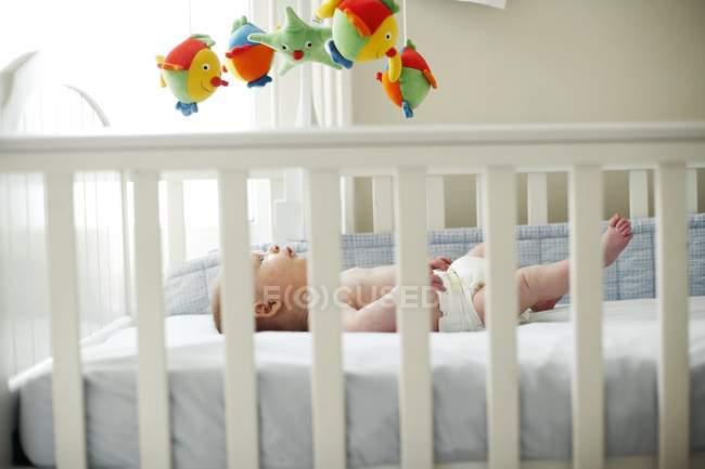 Infantil menino deitado em berço. — Fotografia de Stock