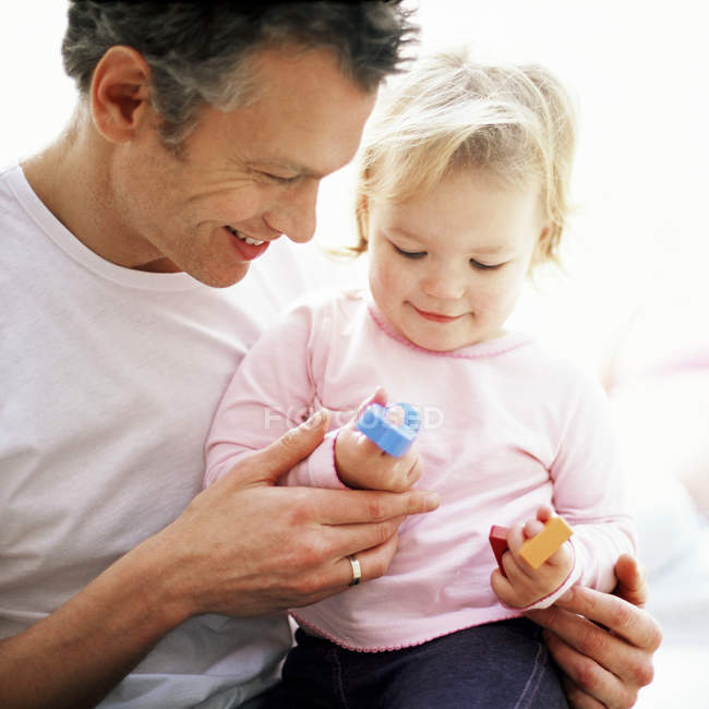 Father playing with toddler daughter on lap. — Stock Photo