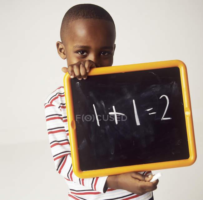 Мальчик младшего возраста держит доску с арифметическим уравнением . — стоковое фото