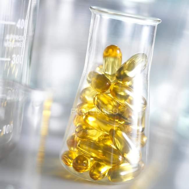 Capsules d'huile de foie de morue en fiole conique . — Photo de stock