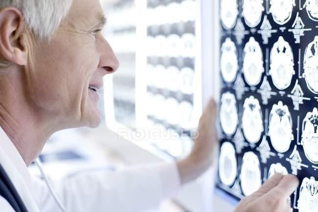 Senior-Radiologe untersucht CT-Scans im Krankenhaus. — Stockfoto