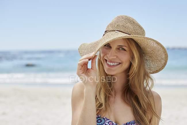 Portrait de femme portant un chapeau de soleil sur la plage . — Photo de stock