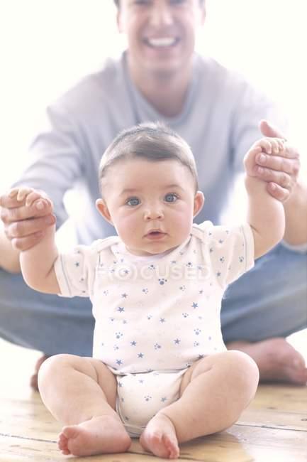 Fier père tenant par la main et en jouant avec le petit garçon. — Photo de stock