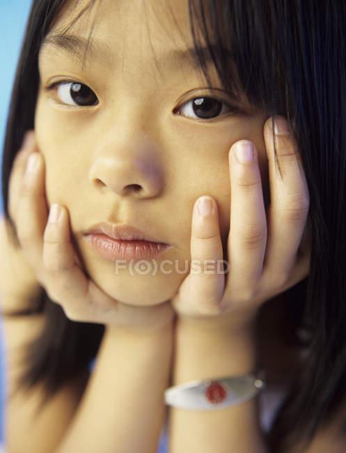 Età elementare ragazza asiatica con cartellino medico guardando in macchina fotografica, ritratto . — Foto stock