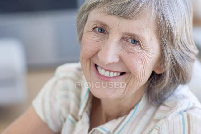 Portrait of happy senior woman relaxing on sofa. — Stock Photo