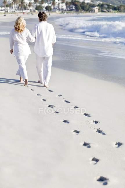 Пожилые пары, ходить на пляж песок с следы. — стоковое фото